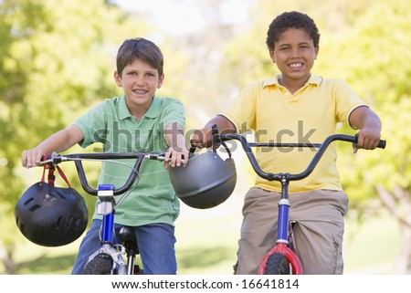 Two young boys on bicycles outdoors smiling