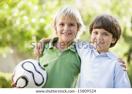 Two young boys outdoors with soccer ball smiling - stock photo