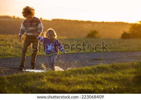 two young boys playing and jumping over puddles at sunset