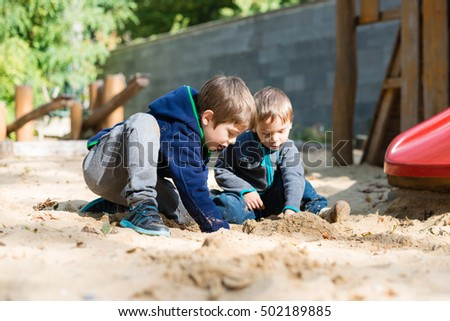 Two young boys playing in a sandpit