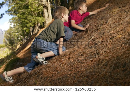 Two young boys prone to the earth creeping their way up a steep bank in a forest or woodland - stock photo