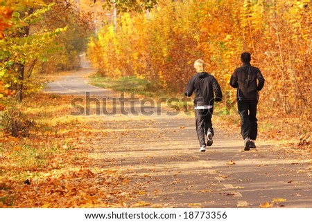 Two young boys run in the park.