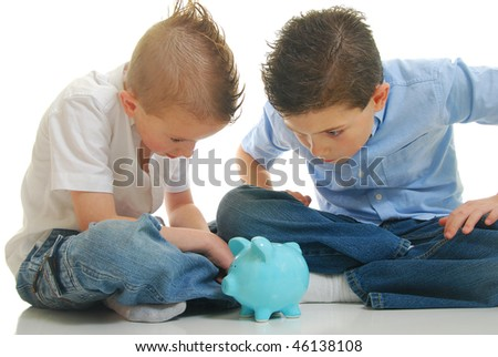 two young boys staring at piggy bank isolated on white. - stock photo