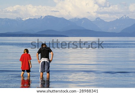 two young boys wading in the ocean - stock photo