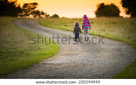 two young boys walking together down a path towards the setting sun - stock photo