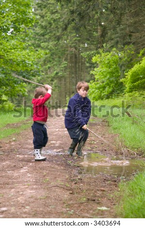 Two young brothers having fun splashing in a muddy puddle.