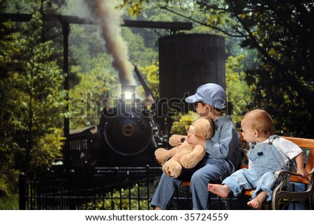 Two young brothers on a park bench straining to see an old-fashioned locomotive coming down the track. - stock photo