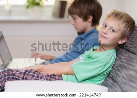 Two young brothers playing on a laptop computer as they sit side by side on a comfortable sofa with one turning to smile at the camera