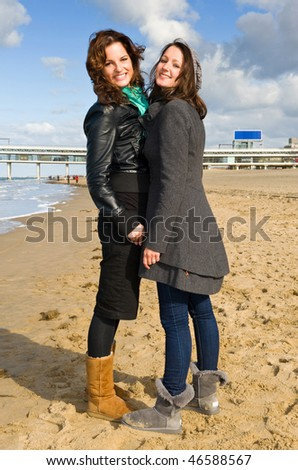 Two young brunette women on the beach on a beautiful autumn afternoon - stock photo