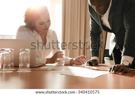 Two young business colleagues working on some business ideas. Entrepreneurs analyzing business reports on conference table. - stock photo