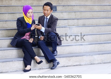 Two young business executive discussing using tablet phone while seating at stair