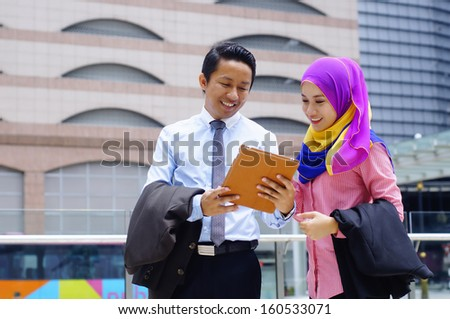 Two young business executive using tablet computer outdoor