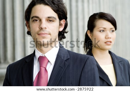 Two young business executives standing in front of an old building