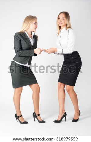 Two young business ladies argue because of paper money - stock photo