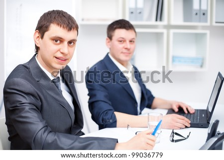Two young business men working together at office - stock photo