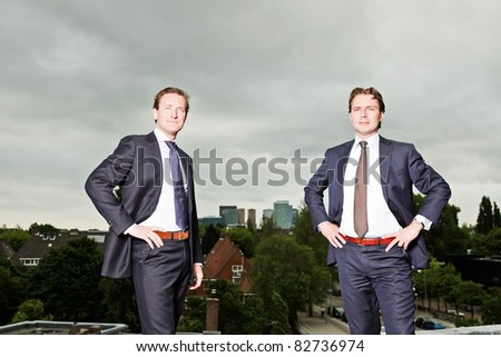 Two young business outdoors on top of building with cloudy sky. - stock photo