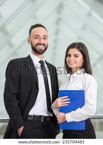 Two young business people at work in modern office is looking at camera. - stock photo