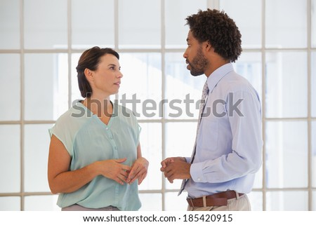 Two young business people having a conversation in the office - stock photo