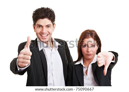 Two young business people holding their thumbs up and down - stock photo