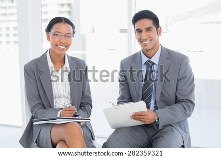 Two young business people in board room meeting at office - stock photo