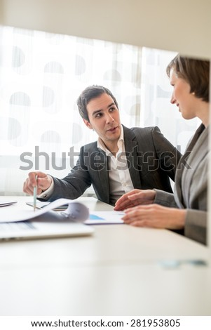 Two Young Business People in Corporate Attire Discussing Some Plans at the Table with Plenty of Documents. - stock photo