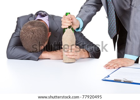 Two young business people in elegant suits sitting at desk drunk with bottle of wine. Isolated over white background. Alcoholism concept. - stock photo