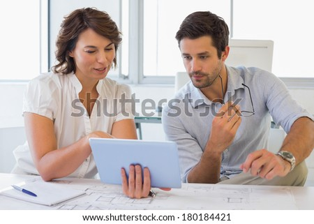 Two young business people looking at digital tablet in the office