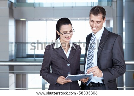 Two young business people looking documents - stock photo
