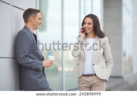 Two young business people on the coffee break in front of the office building - stock photo