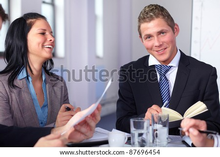 Two young business people sitting at table and have laugh while working on some paperwork - stock photo