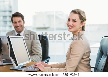Two young business people using computer in office - stock photo