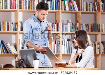 Two young business people, wearing in casual clothes, are discussing while man is showing something on digital tablet, on the bookshelves background, in office, waist up