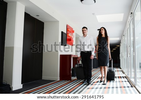 two young business person man and woman walking in a public space corridor - stock photo