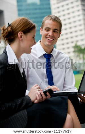 Two young business professionals sitting outside with a laptop computer - stock photo