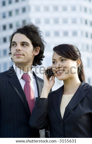 Two young business professionals standing in front of city skyscraper