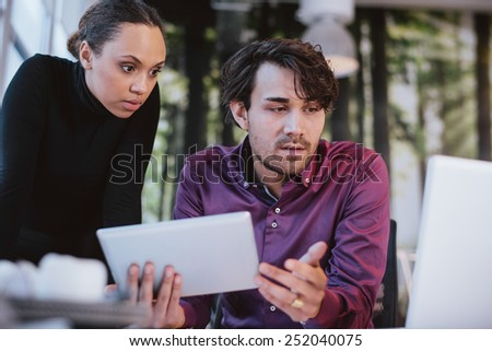 Two young business professionals working together on a project. Creative executives using digital tablet and laptop for searching information on internet. - stock photo