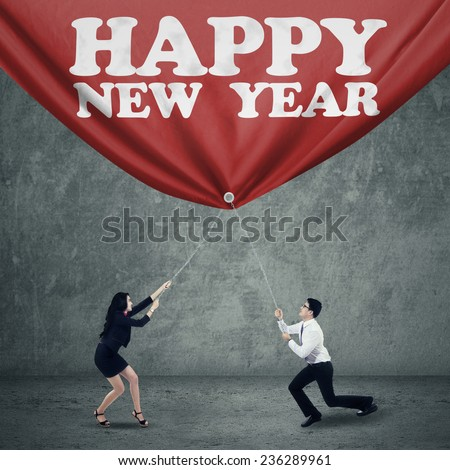 Two young business team drag a banner with a text of happy new year  - stock photo