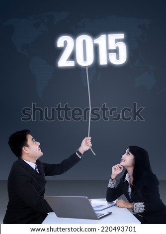 Two young business team in office meeting, pulling number 2015