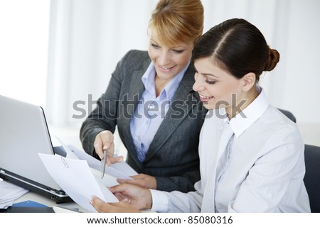 two young business woman or office workers discussing paperwork - stock photo
