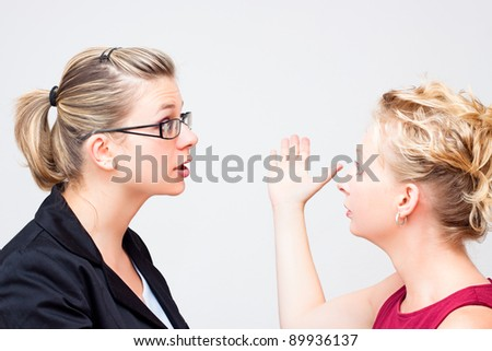 Two young business women conflict. - stock photo