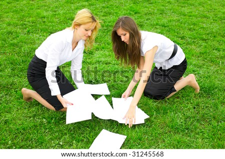 Two young business women gather around on the grass paper