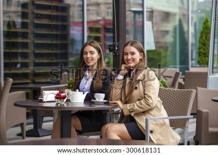 Two young business women having lunch break together in a coffee shop - stock photo