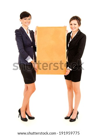 two young business women holding the cork board, white background, full length