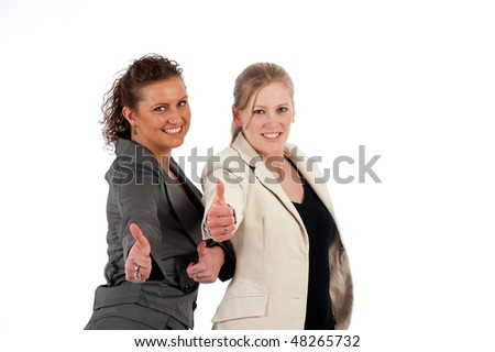 Two young business women show the thumbs -