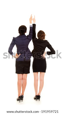 two young business women standing back and pointing up, white background - stock photo