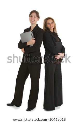 Two young business women standing with laptops and smiling.  Isolated on white background. - stock photo