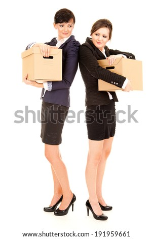 two young business women with carton boxes, standing and smiling, white background - stock photo