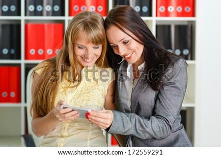 Two young business women with mobile phone in the office. - stock photo