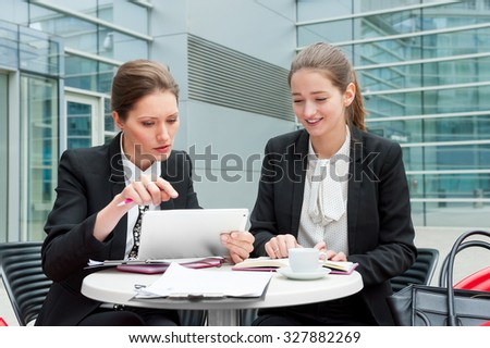 Two young business women works together - stock photo