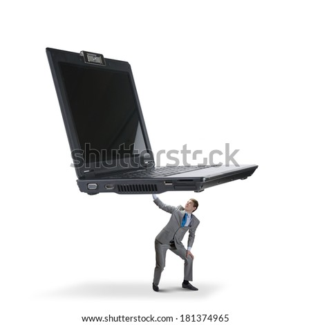 Two young businessman lifting huge laptop above head - stock photo